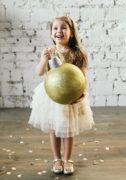 Светлое платье на девочку з золотистыми паетками и фатиновой юбочкой